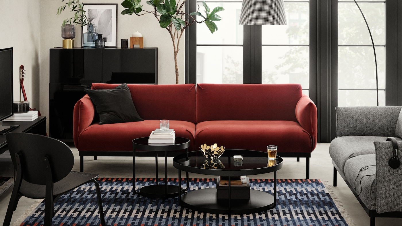 Two ÄPPLARYD sofas, one red and one grey in a bright living room around two black coffee tables, with an easy chair opposite.