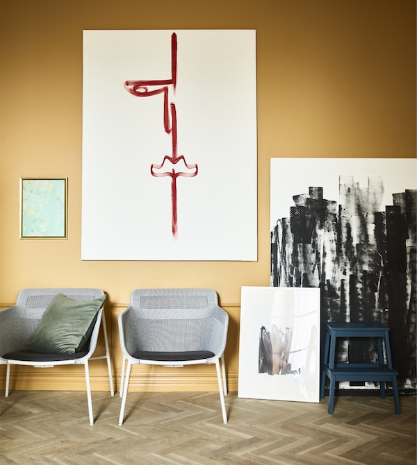 Two armchairs and canvases of art sit against a wall.