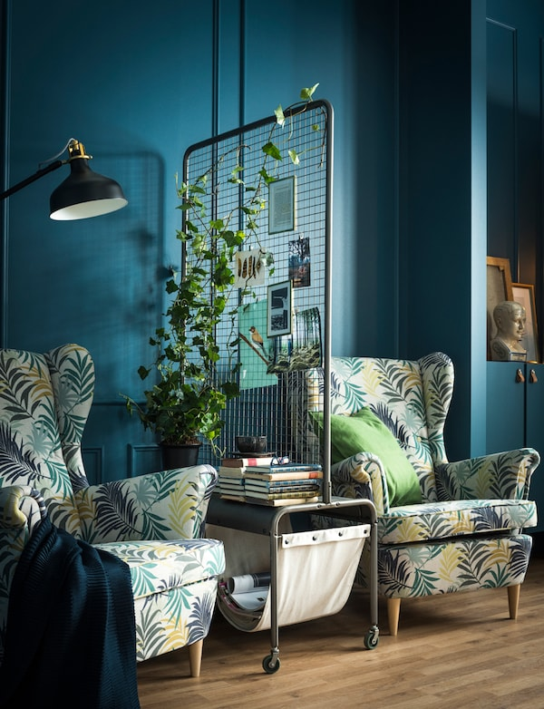 Two armchairs are separated by a room divider holding a plant, magazine and book storage.