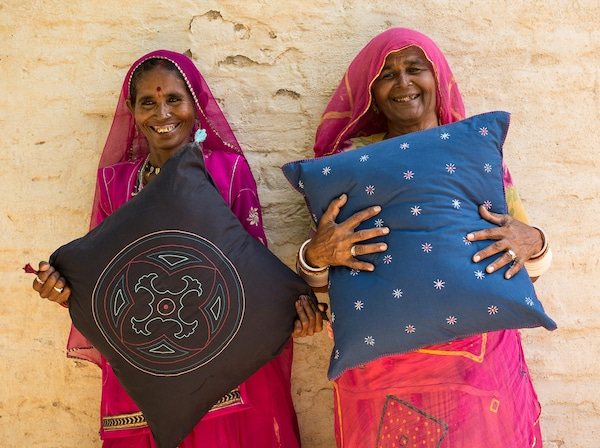 Two artisan women working with a social entrepreneur in India are holding up the handcrafted pillows they made for IKEA.