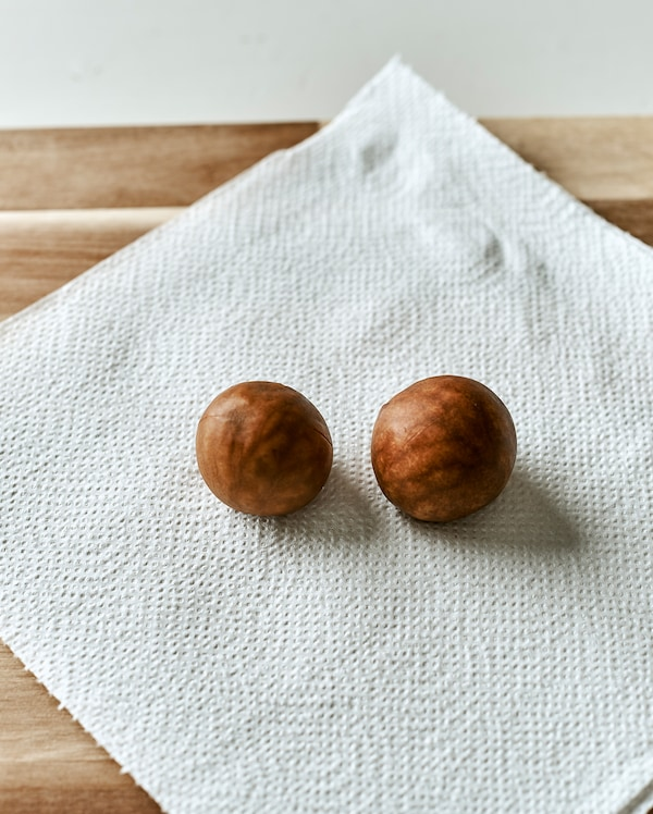 Two avocado seeds placed on a sheet of kitchen paper on a wood chopping board.