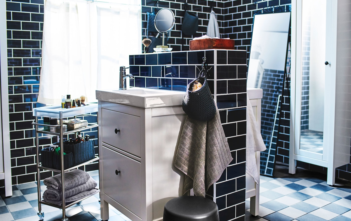 Two bathroom sinks and washstands mounted back to back in the centre of a large, black tiled bathroom.