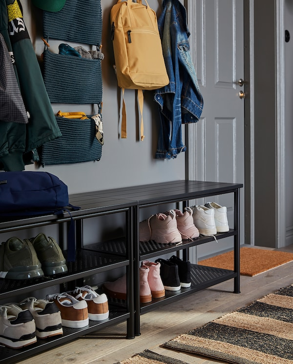 Two benches with shoe storage stand next to each other. Many shoes are stored on the shelves and jackets and bags hang above.