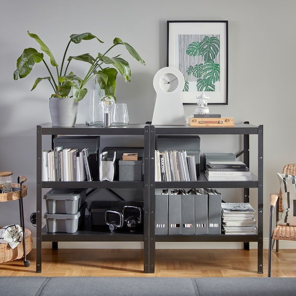 Two black and sturdy BROR shelving units that hold lots of decorative items, books, magazine files, kettlebells and more.