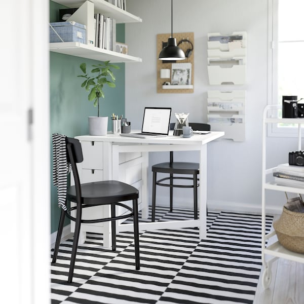 Two black chairs are placed surrounding a White NORDEN table in the center, and a laptop is on top..