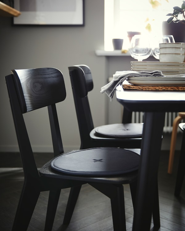 Two black chairs with round, dark grey chair pads stand by a black table where wine glasses and grey dinnerware stand.
