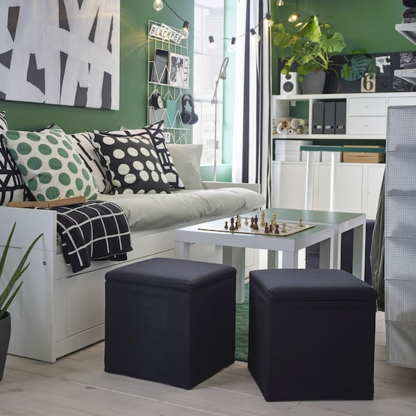 Two black footstools stand by two side tables and a day-bed and offer extra seating. A chessboard stands on the table.