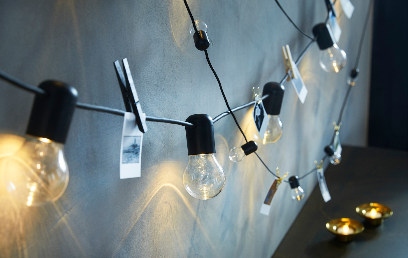 Two black lighting chains hanging from a wall with small illustrations clipped to the cords between the bulbs.