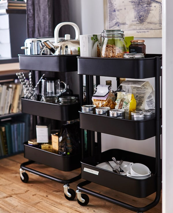 Two black RÅSKOG kitchen trolleys stocked with kitchen supplies, including food, a toaster, a kettle, and dishes.