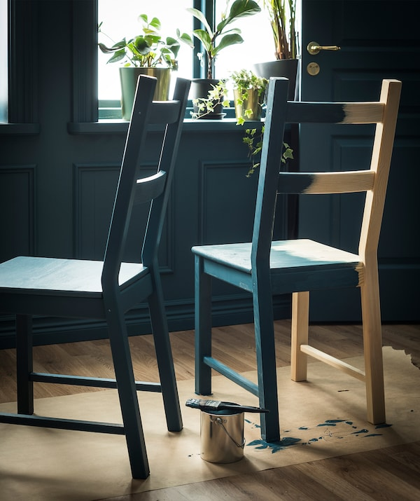 Two blond-wood chairs placed on floor-protective paper. Otherwise untreated, the chairs are being painted in a dark shade.