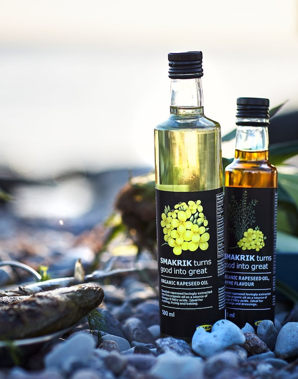 Two bottles of IKEA SMAKRIK organic rapeseed oil standing among pebbles in the evening light.