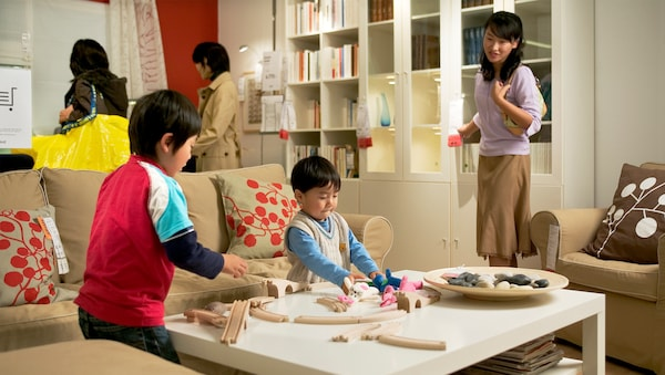 Two boys are playing with toys on a table while a woman in a purple shirt is watching them beside the sofa in the showroom.