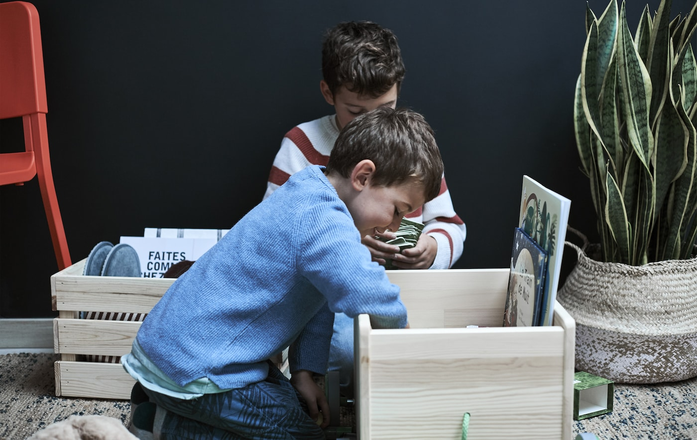 Two boys looking inside a wooden box filled with objects.