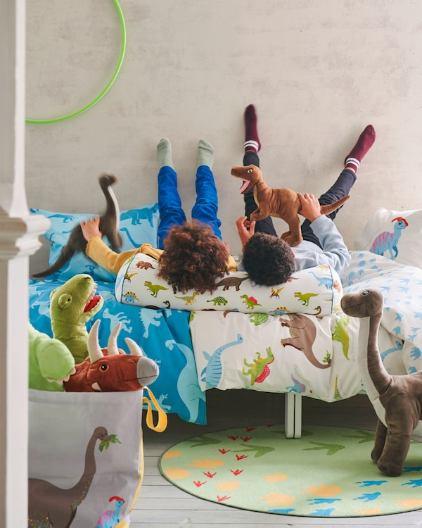 Two boys lying with their heads on JÄTTELIK cushion in a bed made with JÄTTELIK textile series with a dinosaur pattern.