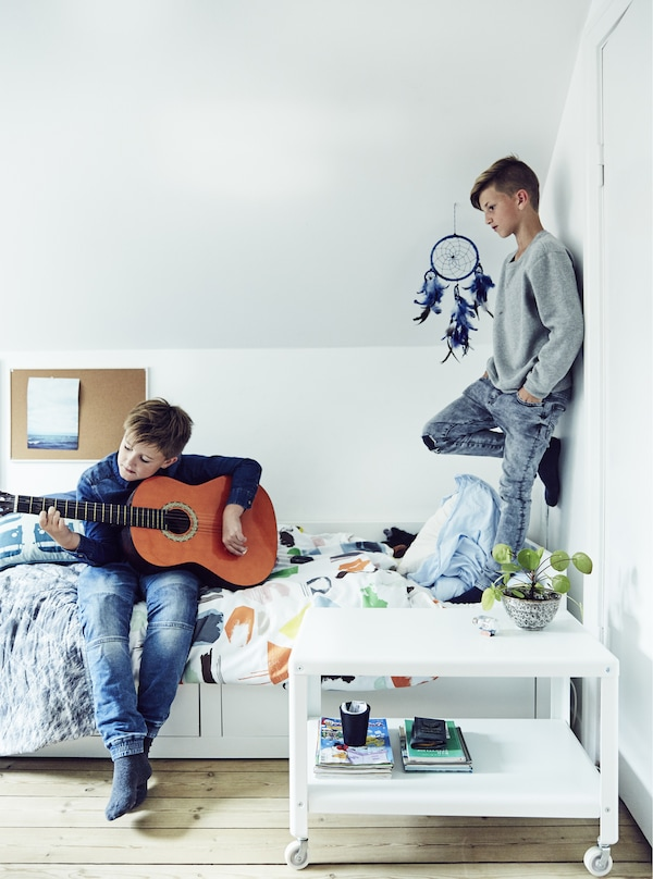 Two boys playing in a child's bedroom.