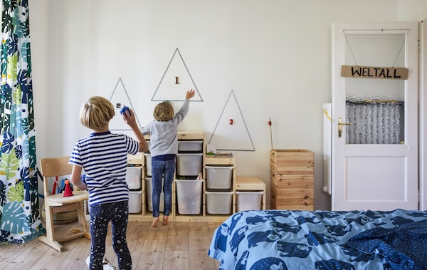 Two boys playing in a room with toy storage units against the wall.