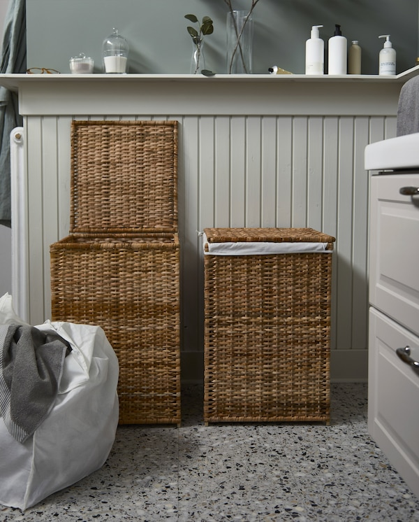 Two BRANÄS rattan laundry baskets with linings. One basket is open, and its lining with laundry inside stands next to it.