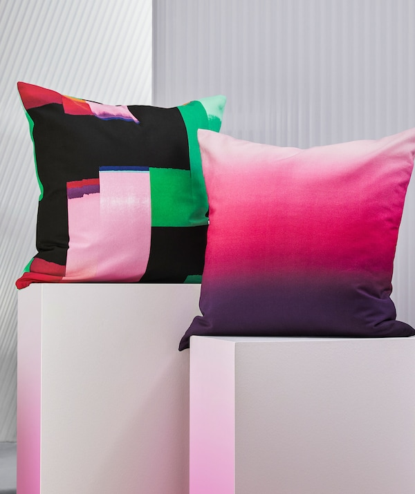 Two brightly-coloured cushions on white pedestals.