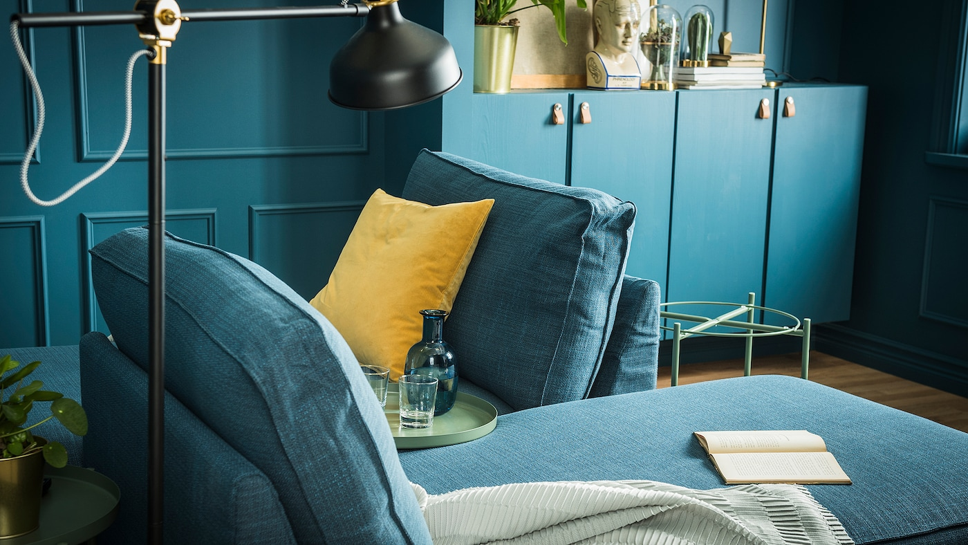 Two chaise longues furnishing a living room that's painted in deep shades of blue.