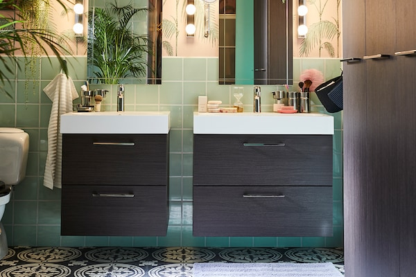 Two charcoal bathroom vanities against a green tiled wall.