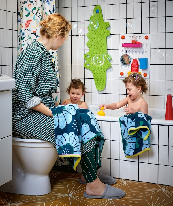 Two children in a white tiled bath and a woman sitting on the lid of a toilet next to them.