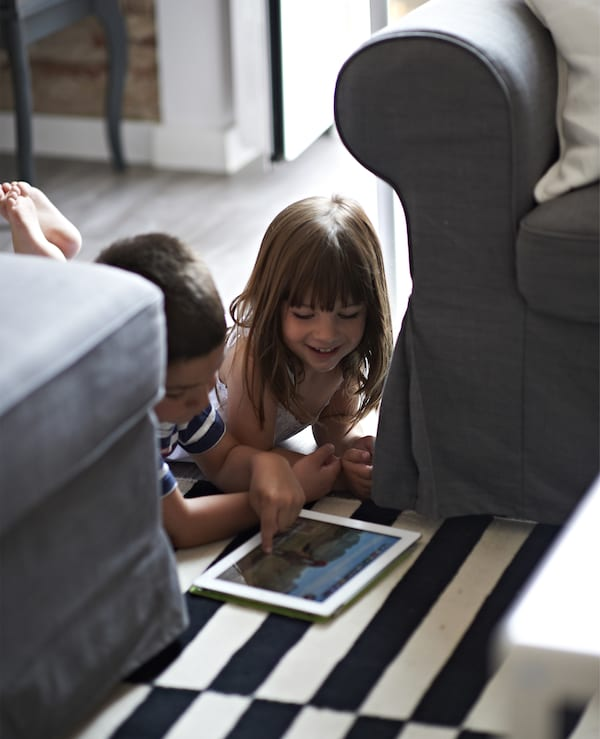 Two children laying between two sofas on the floor playing with a touch-screen device.
