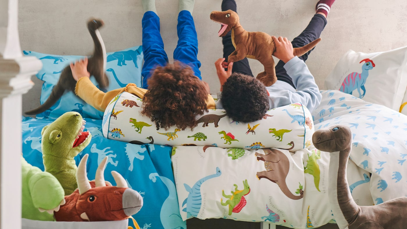 Two children lying on a bed with JÄTTELIK bed linen with dinosaur prints while playing with JÄTTELIK dinosaur soft toys.