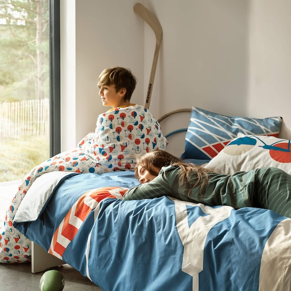 Two children on a bed surrounded by toys