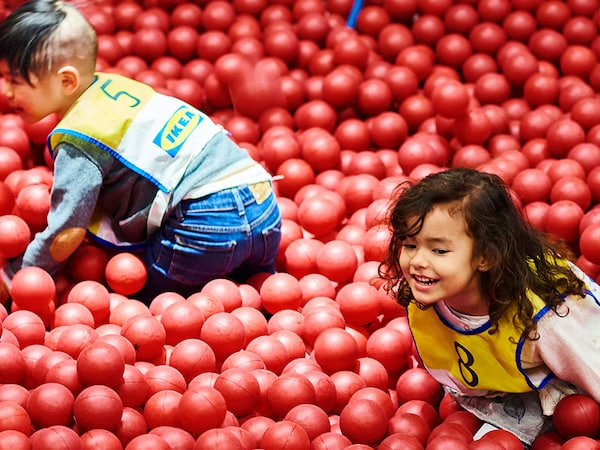 Two children play in a ball pit filled with red plastic balls at Småland.