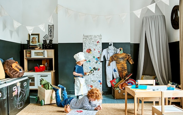 Two children playing in a room with small table and chairs, blackboard, miniature kitchen and bunting.