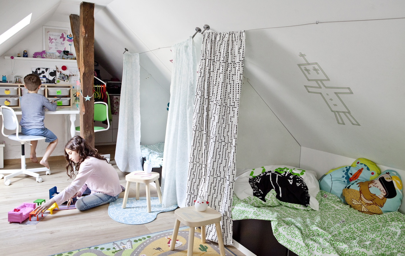 Two children playing in a shared bedroom with a sloped ceiling.