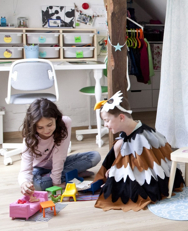 Two children playing on the floor of their shared bedroom.