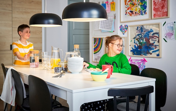 Two children sitting at a large white dining table with balck pendant lights and a wall of framed children's art behind them.