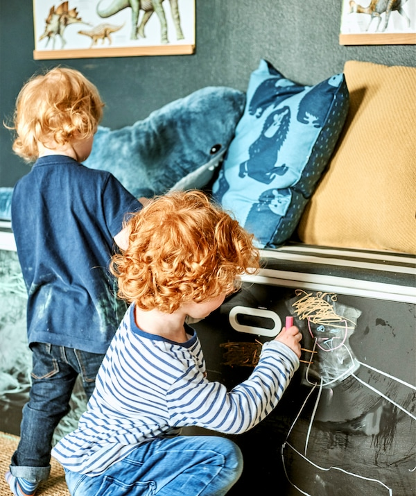 Two children using chalk to draw on a set of drawers with chalkboard paint door fronts.