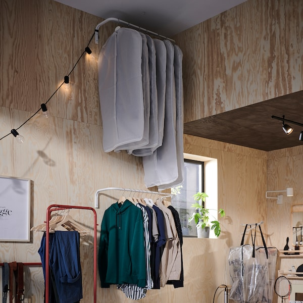 Two clothes bars are wall-mounted. One is by the ceiling and stores clothes in clothes covers, and one is lower and in reach.