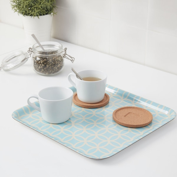 Two coffee cups on a light blue SOLGLIMTAR tray with a jar of tea in the background.