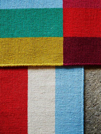Two colourful rugs placed one on top of another.