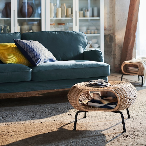 Two curved GAMLEHULT footstools, handmade from rattan, with wide side openings for storage, in a living room with a blue sofa.