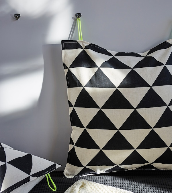 Two cushions with a black and white irregular print hung on a wall.