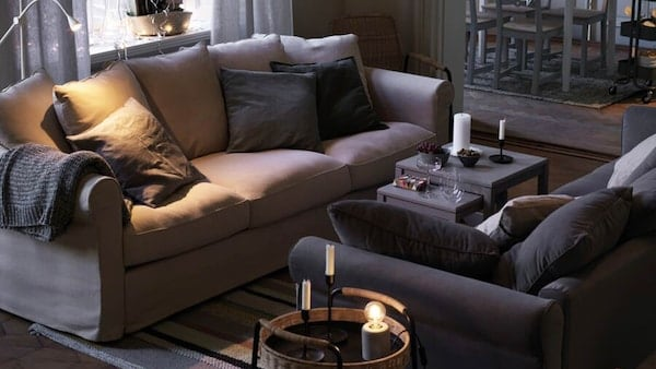 Two dark colored sofas facing each other in a living room with light shining in from a nearby window.