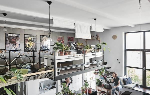 Two desks and plants on a mezzanine level.
