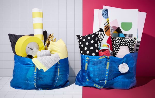 Two different colourful looks inside two blue bags (FRAKTA) that contain all of the products needed for the two interior styles.