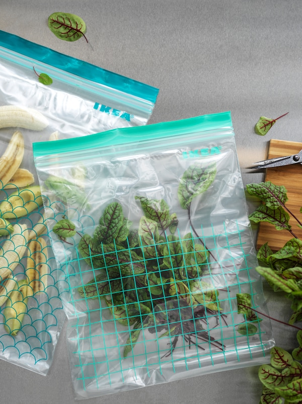 Two different-size ISTAD resealable plastic bags, one filled with chopped up bananas and the other beet leaves.