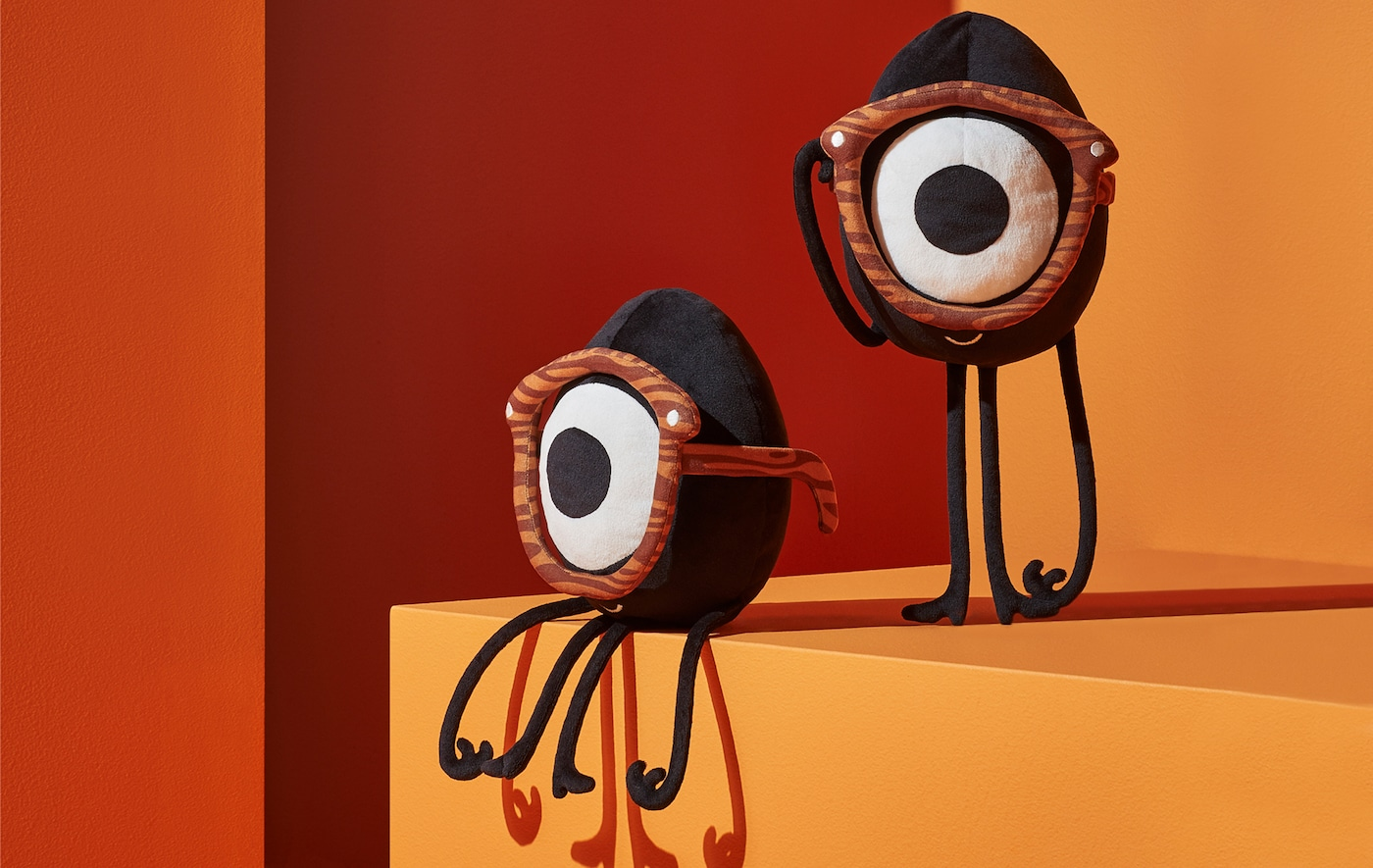 Two egg-shaped soft toys, each with one eye and a monocle, on an orange and red backdrop.