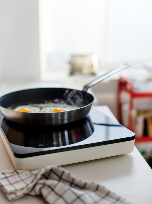 Two eggs frying in a pan on a TILLREDA portable induction hob set on a worktop, a kitchen towel lying beside it.