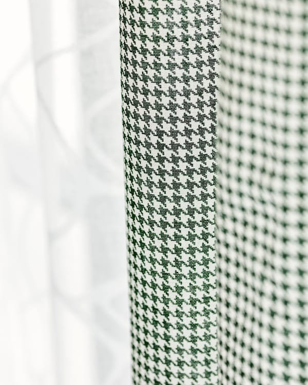 Two fabric curtains hung side by side, one in sheer white cotton, one in green and white check.