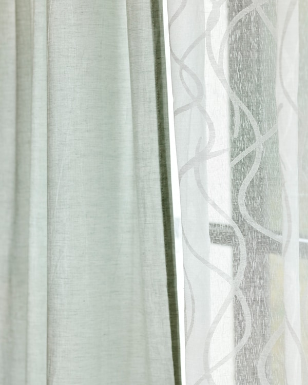 Two fabric curtains hung side by side, one in sheer white cotton, one in light green linen.