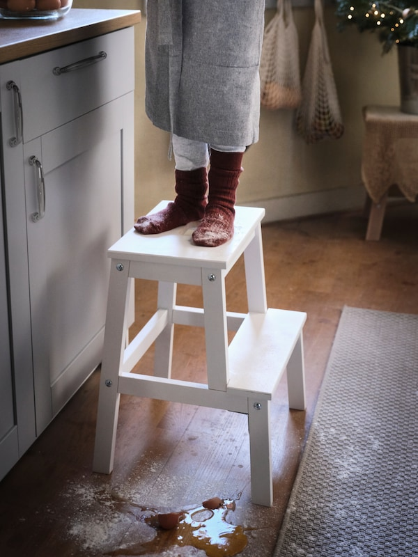 Two feet covered in white flour are stood on a BEKVÄM step stool in a traditional-looking kitchen.