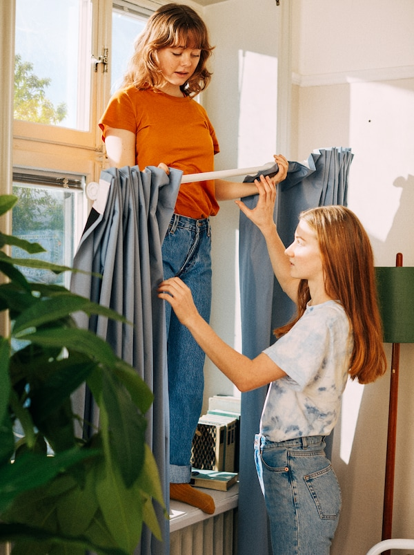 Two female students stand in front of a window while preparing to install curtains using a shower curtain rod.