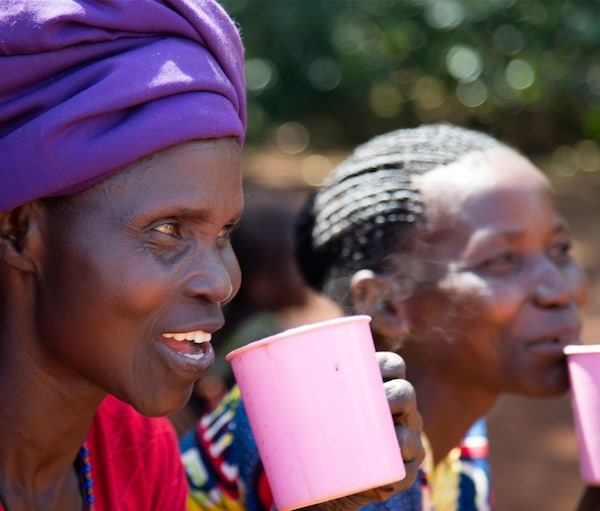Two female workers from the White Nile coffee project in Uganda having coffee during a break.